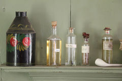 Herbs on a shelf. Decorative metal canister with glass bottles of herbs on a shelf Stock Photography