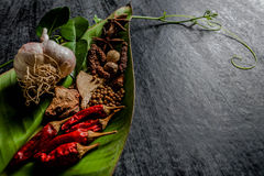 Herbs and spices around empty cutting board on dark stone backgr Stock Photo