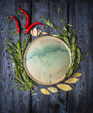 Herbs and spices around platte on dark blue wooden background, top view Stock Photography