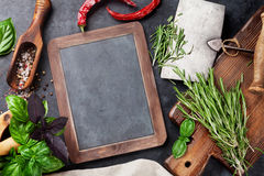Herbs and spices. Cooking on stone table. Basil, rosemary, pepper and salt. Top view with blackboard for your text stock photography