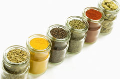 Herbs and spices in glass jars, isolated on white background Royalty Free Stock Photo