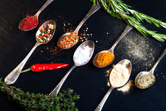 Herbs and spices with old metal spoons on a black background. To Stock Image