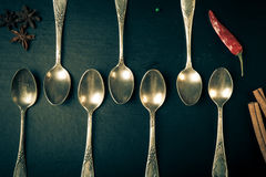 Herbs and spices with old metal spoons on a black background. To Stock Photo