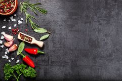 Herbs and spices over black stone background. Top view with copy space. Stock Photo