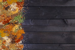 Herbs and spices over black wooden background. Top view with copy space. Various spices on wooden background. Top view with copy space Stock Image