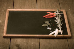 Herbs and spices. Red pepper, salt and rosmary on a black backgr Royalty Free Stock Image