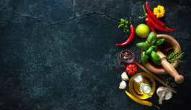 Herbs and spices on slate background. Herbs and spices with olive oil on slate background Royalty Free Stock Photography