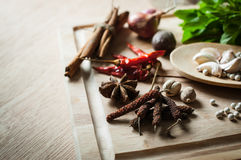 Herbs and spices on wood chopping block Royalty Free Stock Image