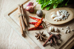 Herbs and spices on wood chopping block Stock Photos