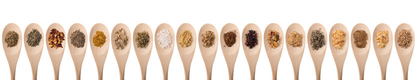 Herbs and spices. On wood spoons isolated on a white background stock images