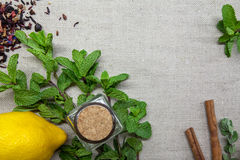Herbs for tea and a lemon on a linen background. Herb and spice ingredients on a grey background Royalty Free Stock Images
