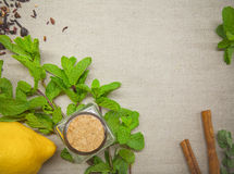 Herbs for tea and a lemon on a linen background. Herb and spice ingredients on a grey background Royalty Free Stock Photo