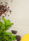 Herbs for tea and a lemon on a linen background. Herb and spice ingredients on a grey background royalty free stock photography