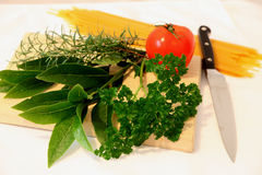 Herbs and tomato. On wooden chopping board Royalty Free Stock Images