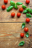 Herbs and tomatoes. Fresh leaves of basil placed with cherry tomatoes on wooden background Royalty Free Stock Photography