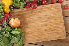 Herbs and vegetables with a blank chopping board. Space for copy Royalty Free Stock Photos
