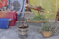 Herbs and wine press. Outdoor scene with an antique wine press and some herbs inside baskets Stock Images