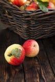 Herbstäpfel in einem Korb auf einem hölzernen Hintergrund Stockfoto