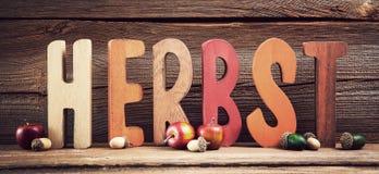 Herbst hintergrund. Buchstaben ergeben das wort herbst vor holzhintergrund stock photo