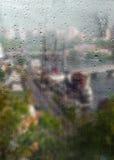 Herbst, regnerische Stadt durch ein Fenster mit Regentropfen Lizenzfreie Stockfotos