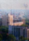 Herbst, regnerische Stadt durch ein Fenster mit Regentropfen Stockbilder