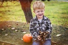 Herbst Schöner lächelnder blonder Junge hält ein Blatt Stockfotografie