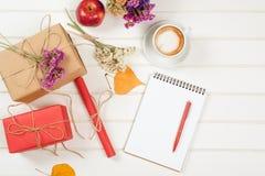 Herbst-themenorientierte Handwerksgeschenkboxen, verzierte gelbe Blätter, Blumen Eine Schale Cappuccino und Notizbuch mit Bleisti Lizenzfreies Stockfoto