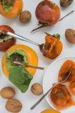 Herbst trägt Hintergrund - rohe Persimonen und Nüsse auf weißem Hintergrund Früchte stockfotos