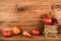 Herbstanordnung - Topf mit künstlichem granat, Kegel und Kürbisen auf hölzernem Hintergrund Stockfotos
