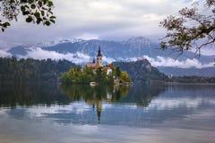 Herbstansicht der historischen Kirche auf der Insel im See blutete, bevor Schnee Alpen mit einer Kappe bedeckte lizenzfreies stockfoto
