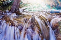 Herbstansicht des kleinen Wasserfalls mit reinem Wasser bei Sonnenuntergang Lizenzfreie Stockfotos