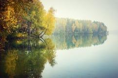 Herbstbäume, die über See nachdenken stockfoto