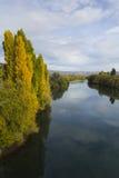 Herbstbäume durch einen Fluss Lizenzfreies Stockfoto