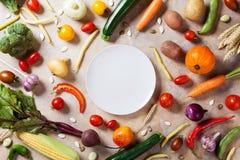 Herbstbauernhofgemüse, Wurzelgemüse und Draufsicht der weißen Platte mit Kopienraum für Menü oder Rezept Gesundes Lebensmittel au stockfotografie