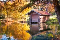 Herbstblockhaus auf See Stockfoto