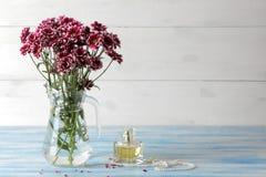 Herbstblumen der Chrysantheme in einem Krug und in einem Parfüm auf einem blauen Holztisch lizenzfreies stockbild