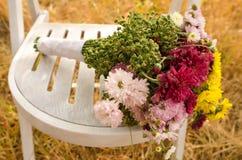 Herbstblumenstrauß auf einem weißen Stuhl Stockfotos
