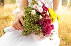 Herbstblumenstrauß in den Händen Lizenzfreie Stockfotos