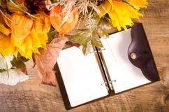 Herbstblumenstrauß mit Tagebuch auf Holztisch Lizenzfreie Stockbilder