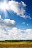 Herbstfeld und -himmel mit Sonne Stockbild
