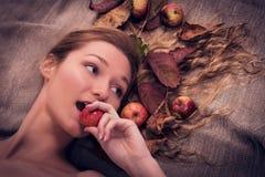 Herbstfrau, die auf dem Segeltuch mit Fallblättern und -früchten in ihrem Haar, einen Apfel beißend liegt Lizenzfreie Stockfotografie