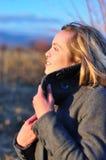 Herbstfrau, die Sonnenuntergang genießt Stockbild
