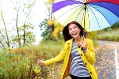 Herbstfrau glücklich im Regen, der mit Regenschirm läuft Stockfoto