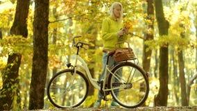Herbstfrau im Herbstpark mit grünem Pullover enjoy Sorglose Frau Alte Fahrradlenkstange der Mädchenarmholding mit stock video