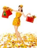 Herbstfrau mit Einkaufstaschen im Kleid des Ahorns. Weißer Hintergrund Stockbilder