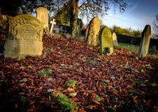 Herbstfriedhof, der alte Gräber innerhalb eines Teppichs von gefallenen Blättern zeigt Lizenzfreie Stockfotos