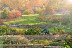 Herbstgarten mit Rasen, Stützmauern, alpines Dia, Sonne gla Stockfoto