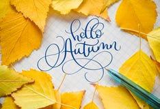 Herbstgelb verlässt mit Wanne auf Blatt Papier und Text hallo Herbst in der Mitte Lizenzfreies Stockbild