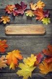 Herbsthintergrund mit Schild, orange Blatt auf altem Schmutzholz Stockbild