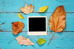 Herbsthintergrund mit trockenen Blättern und leeren Fotorahmen Lizenzfreies Stockfoto